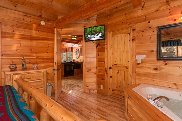 bedroom with wall mount television and jacuzzi tub at alpine sondance a 2 bedroom cabin rental located in pigeon forge