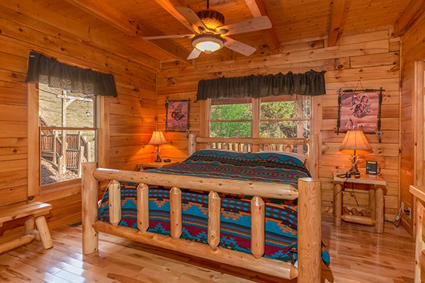 king sized log bed and bench seat at alpine sondance a 2 bedroom cabin rental located in pigeon forge