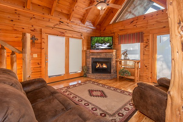 stone fireplace with television and deck access at alpine sondance a 2 bedroom cabin rental located in pigeon forge