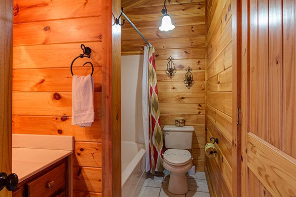 bathroom with a tub and shower at alpine sondance a 2 bedroom cabin rental located in pigeon forge