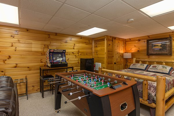 Downstairs bedroom with foosball and arcade game at Kelly's Cabin, a 1 bedroom cabin rental located in Pigeon Forge