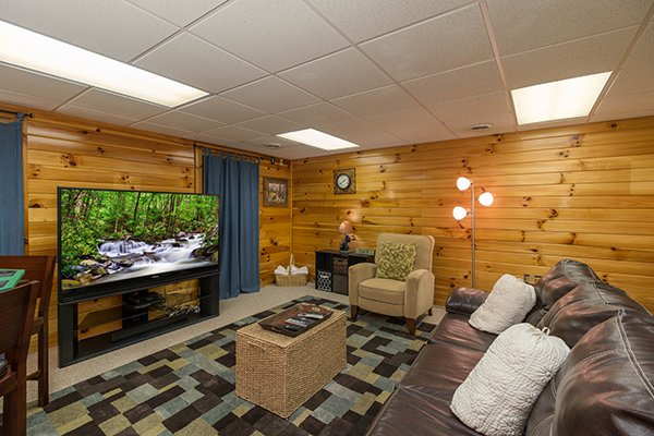 Big screen TV and sitting area on the lower floor at Kelly's Cabin, a 1 bedroom cabin rental located in Pigeon Forge