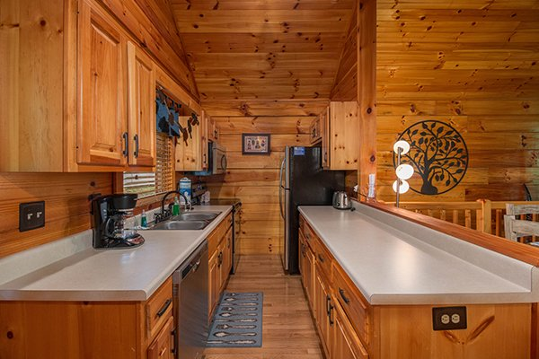 Galley kitchen with black appliances at Kelly's Cabin, a 1 bedroom cabin rental located in Pigeon Forge