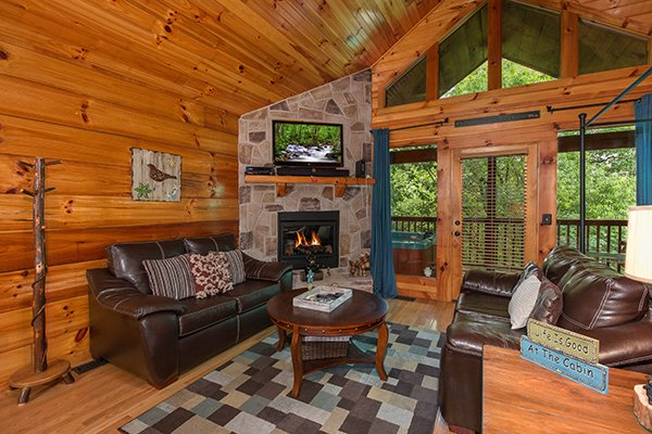 Living room with fireplace, TV, and deck access at Kelly's Cabin, a 1 bedroom cabin rental located in Pigeon Forge