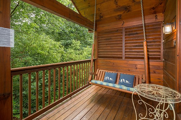 Swing on a covered porch at Kelly's Cabin, a 1 bedroom cabin rental located in Pigeon Forge