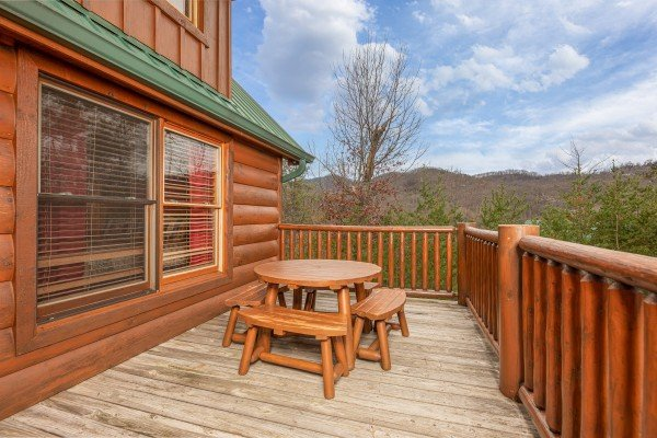 Picnic table on the deck at True Grit, a 5 bedroom cabin rental located in Pigeon Forge