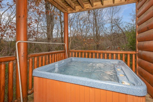 Hot tub on a covered porch at True Grit, a 5 bedroom cabin rental located in Pigeon Forge