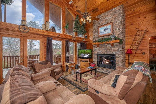 Living room with fireplace, TV, and lots of windows at True Grit, a 5 bedroom cabin rental located in Pigeon Forge