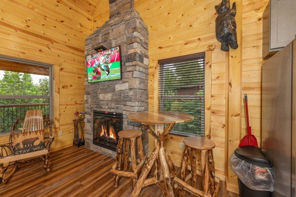 Bistro table and fireplace at Pool & a View, a 2 bedroom cabin rental located in Gatlinburg