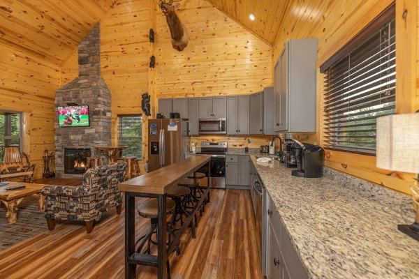 Breakfast bar for four in a kitchen with granite counters at Pool & a View, a 2 bedroom cabin rental located in Gatlinburg