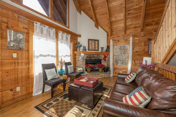 Two chairs, a sofa, and fireplace in a living room at Brink of Heaven, a 2 bedroom cabin rental located in Gatlinburg