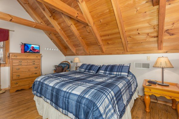 Loft bedroom with dresser, TV, night stands, and lamps at Brink of Heaven, a 2 bedroom cabin rental located in Gatlinburg