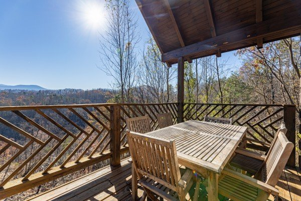 Dining table for six on a covered deck at Brink of Heaven, a 2 bedroom cabin rental located in Gatlinburg