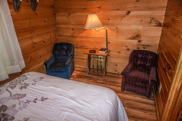 Reading lamp between two chairs at the foot of the bed at Cozy Cabin, a 2-bedroom cabin rental located in Gatlinburg