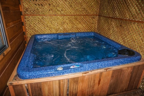 Hot tub in screened in deck at Cozy Cabin, a 2-bedroom cabin rental located in Gatlinburg