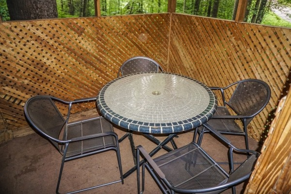 patio chairs and table in screened in deck at cozy cabin a 2 bedroom cabin rental located in gatlinburg