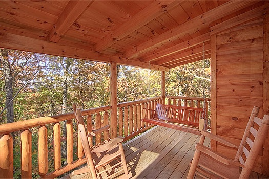 Back deck swing and rockers at Tucked Away, a 2 bedroom cabin rental located in Gatlinburg