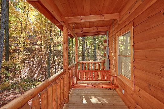 Front porch swing at Tucked Away, a 2 bedroom cabin rental located in Gatlinburg