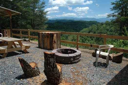 custom tree trunk chairs around a firepit at a panoramic view a 1 bedroom cabin rental located in pigeon forge