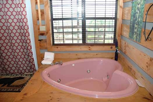 pink heart shaped jacuzzi tub at a panoramic view a 1 bedroom cabin rental located in pigeon forge