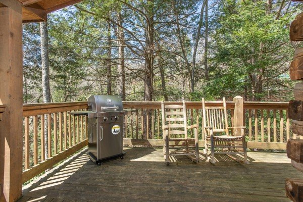 Deck with propane grill and rocking chairs at Owl Be Back, a 2 bedroom cabin rental located in Gatlinburg