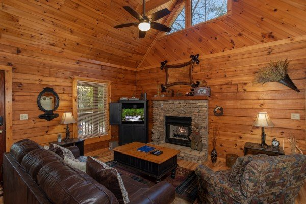 Fireplace and TV in the living room at Owl Be Back, a 2 bedroom cabin rental located in Gatlinburg
