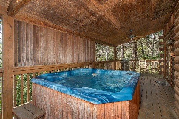 Hot tub on a covered deck at Owl Be Back, a 2 bedroom cabin rental located in Gatlinburg