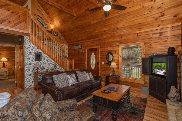 Sofa, chair, and TV in the living room at Owl Be Back, a 2 bedroom cabin rental located in Gatlinburg