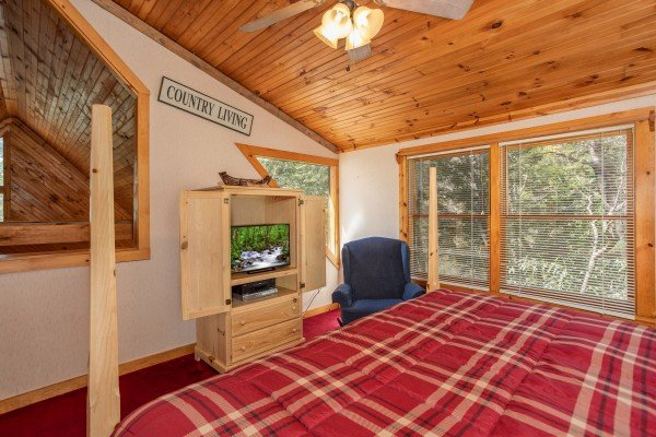 TV and chair in a loft bedroom at Owl Be Back, a 2 bedroom cabin rental located in Gatlinburg