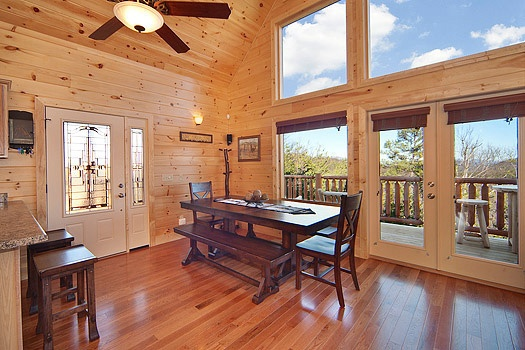 dining table with side bench seats and chairs on the ends at horse'n around a 3 bedroom cabin rental located in pigeon forge