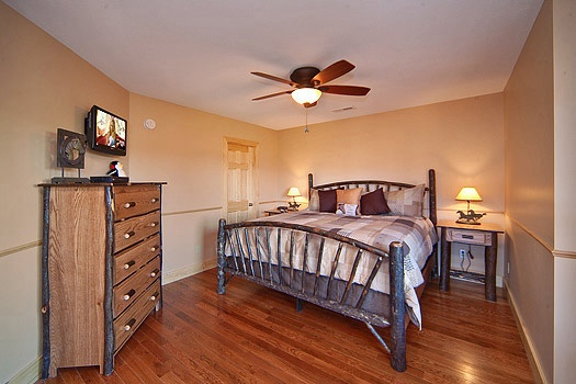 king sized bed with drawers and a ceiling fan in horse'n around a 3 bedroom cabin rental located in pigeon forge