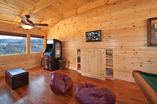 lofted game room with bean bag chairs and arcade cabinet at horse'n around a 3 bedroom cabin rental located in pigeon forge