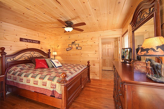 king sized bed in bedroom with ensuite on main level of horse'n around a 3 bedroom cabin rental located in pigeon forge