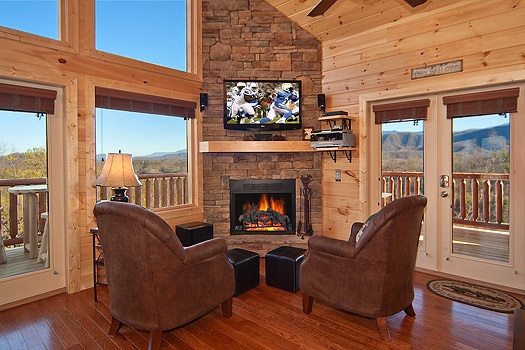 two chairs with foot stools in front of stone fireplace at horse'n around a 3 bedroom cabin rental located in pigeon forge