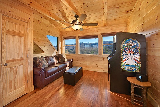 sofa bed across from arcade in lofted game room at horse'n around a 3 bedroom cabin rental located in pigeon forge