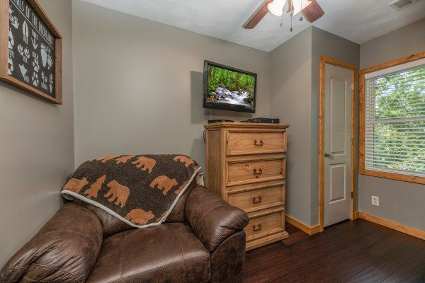 Oversized chair, dresser, and TV in the bunk room at Bear Necessities, a 3 bedroom cabin rental located in Pigeon Forge
