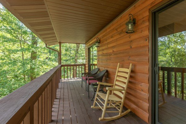 Rocking chair and two chairs on a covered deck at Bear Necessities, a 3 bedroom cabin rental located in Pigeon Forge