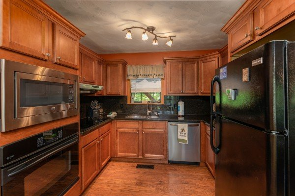 Kitchen with stainless and black appliances at Bear Necessities, a 3 bedroom cabin rental located in Pigeon Forge