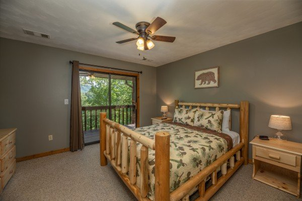 Bedroom with a log bed, night stands, lamps, and deck access at Bear Necessities, a 3 bedroom cabin rental located in Pigeon Forge