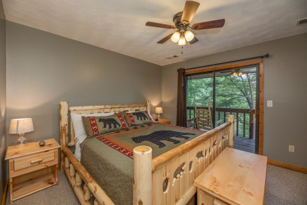 Bedroom with a log bed, night stands, and deck access at Bear Necessities, a 3 bedroom cabin rental located in Pigeon Forge