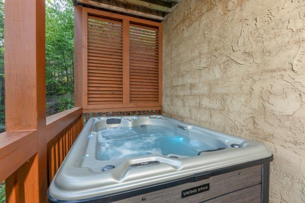 Hot tub on a covered porch at Southern Charm, a 2 bedroom cabin rental located in Pigeon Forge