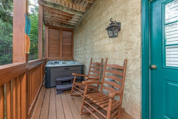 Rocking chairs and a hot tub on the covered deck at Southern Charm, a 2 bedroom cabin rental located in Pigeon Forge