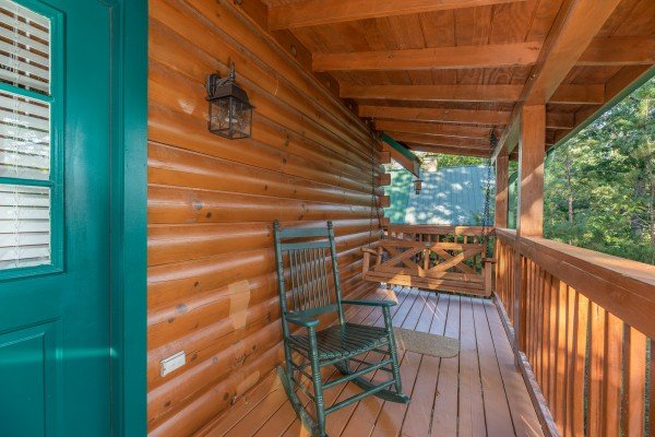 Rocking chair and swing on a covered porch at Southern Charm, a 2 bedroom cabin rental located in Pigeon Forge
