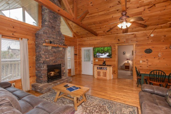 Living room with stacked stone fireplace and television at Bearly in the Mountains, a 5-bedroom cabin rental located in Pigeon Forge