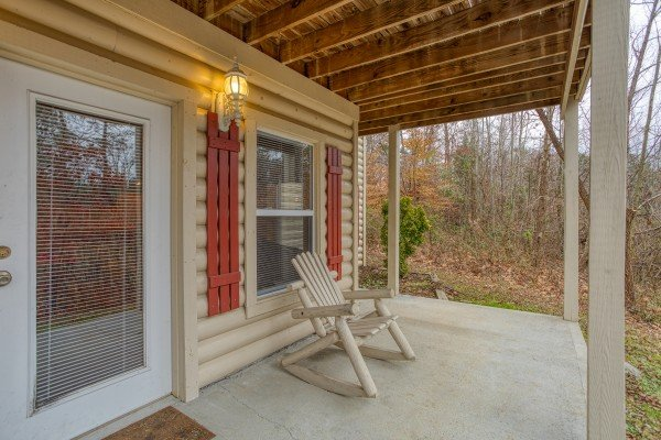 Downstairs porch with a log rocker at Bearly in the Mountains, a 5-bedroom cabin rental located in Pigeon Forge