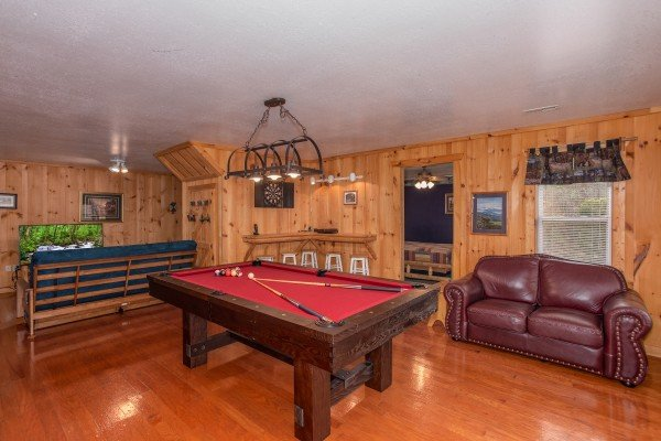 Red felted pool table and a loveseat in the game room at Bearly in the Mountains, a 5-bedroom cabin rental located in Pigeon Forge