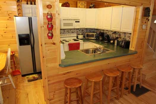 kitchen with bar seating at sweet dreams lodge a 3 bedroom cabin rental located in pigeon forge