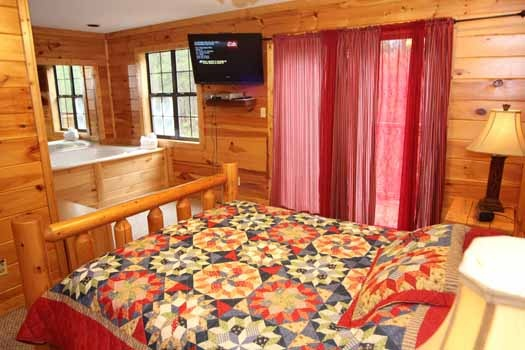 queen bedroom with jacuzzi tub at sweet dreams lodge a 3 bedroom cabin rental located in pigeon forge