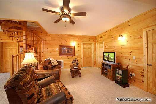 Sofa bed in front of tv in game room at Flying with Eagles, a 3-bedroom cabin rental located in Pigeon Forge