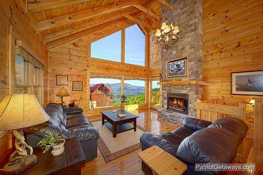 Living room with sofa bed in front of a stone fireplace at Flying with Eagles, a 3-bedroom cabin rental located in Pigeon Forge